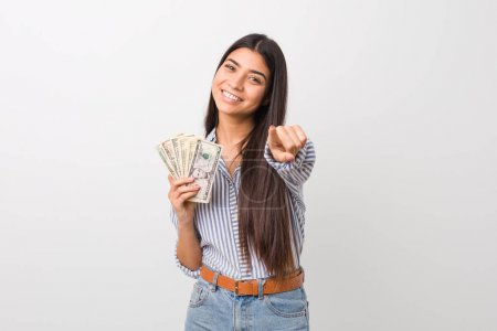 Photo pour Jeune femme arborant des dollars sourires joyeux pointant vers le devant. - image libre de droit