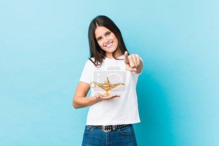 Photo pour Jeune caucasienne tenant une lampe magique sourires joyeux pointant vers l'avant. - image libre de droit