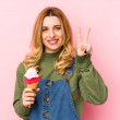 Young blonde woman eating an ice cream isolated sh...
