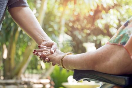 Starsza kobieta na wózku inwalidzkim, trzymając się za ręce z zew młoda kobieta