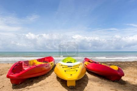 Colorful sea kayaks on sand beach and ocean