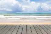 Conceptual wooden deck with blue sky and ocean waves