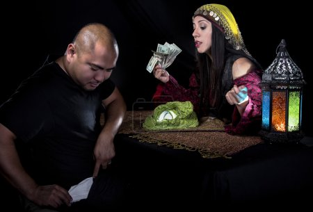 Female fortune teller or con artist swindling money from a male customer via fraud
