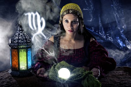 Photo for Psychic or fortune teller with crystal ball and horoscope zodiac sign of Virgo - Royalty Free Image