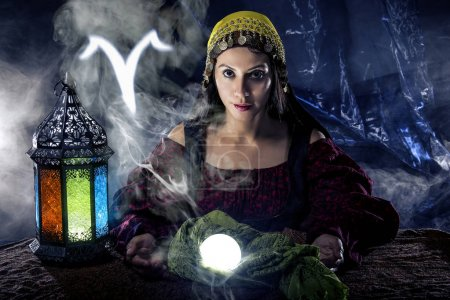 Photo for Psychic or fortune teller with crystal ball and horoscope zodiac sign of Aries - Royalty Free Image