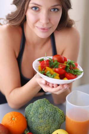 Portrait of smiling young woman with vegetarian vegetable salad.