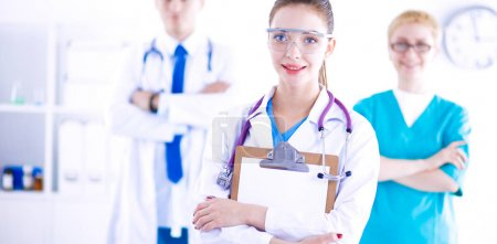 Woman doctor standing with folder at hospital. Woman doctor