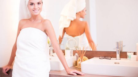 Young attractive woman standing in front of bathroom mirror