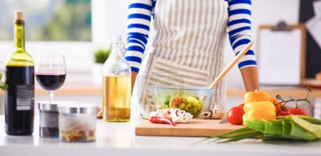 Photo for Young woman mixing fresh salad in kitchen . - Royalty Free Image