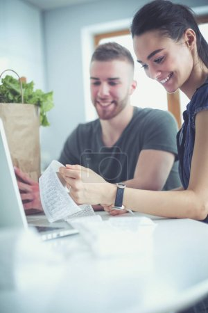 Couple paying their bills with laptop in kitchen at home