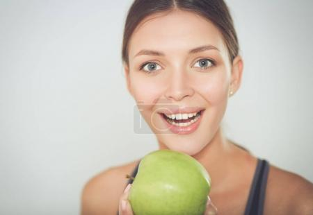 Happy young woman eating apples, isolated on white background.
