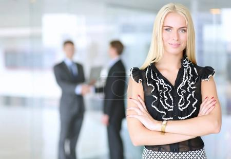 Photo for Portrait of young businesswoman in office with colleagues in the background - Royalty Free Image