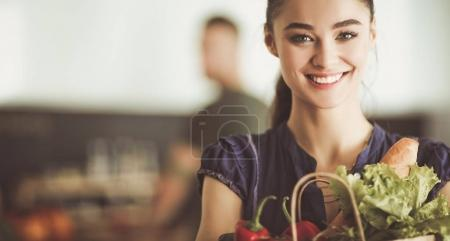 Photo for Young couple in the kitchen , woman with a bag of groceries shopping. - Royalty Free Image