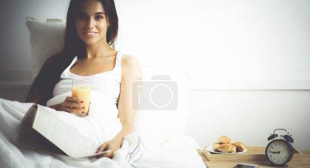 Photo pour Belle jeune femme assise au lit et prenant le petit déjeuner. - image libre de droit