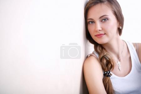 Young woman sitting on the floor near wall . Young...