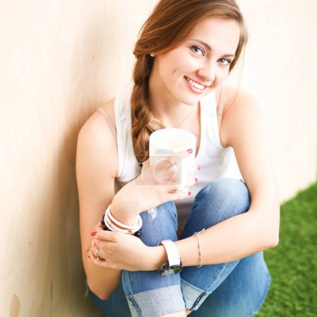 Young woman sitting with book on grass