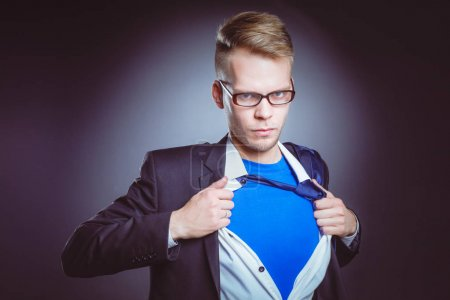 Young businessman acting like a super hero and tearing his shirt, isolated on gray background. Young businessman