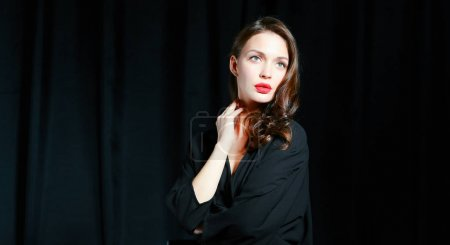 Beautiful woman sitting a chair, isolated on black background