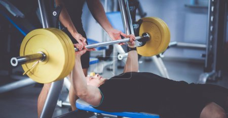 Young man lifting the barbell in gym with instructor