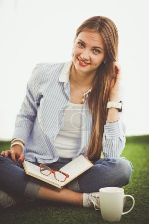 Young woman sitting with book on grass . Young woman