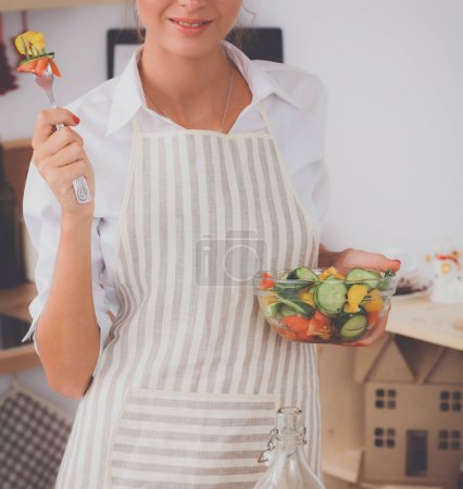 Photo for Young woman eating fresh salad in modern kitchen, isolated - Royalty Free Image