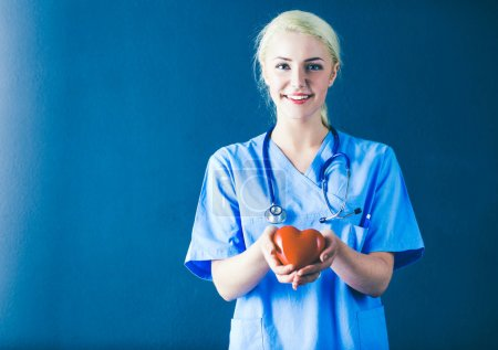 Young doctor woman with stethoscope holding heart