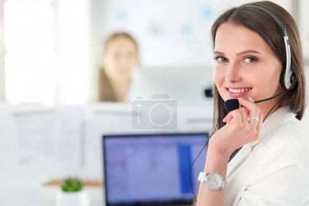 Foto de Sonriendo empresaria o línea de ayuda de operador con auriculares y equipo de oficina. - Imagen libre de derechos