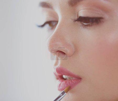 Photo pour Belle fille avec la brosse cosmétique de poudre pour le maquillage. maquillage. Maquillage en appliquant une peau parfaite. - image libre de droit