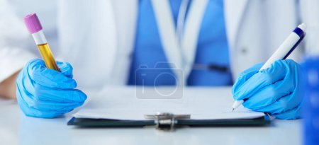 Photo pour Chercheuse est entouré de flacons médicaux et flacons, isolé sur fond blanc. - image libre de droit