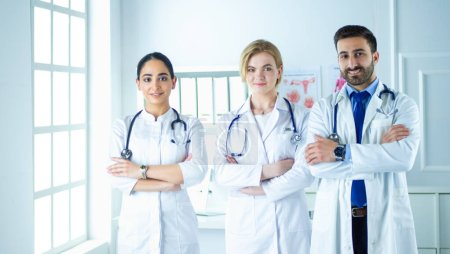 Photo for Successful team of medical doctors are looking at camera and smiling while standing in hospital. - Royalty Free Image