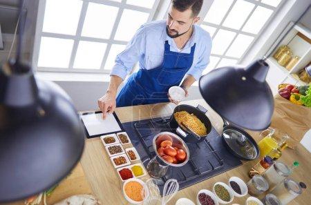 Photo pour Homme de préparer un repas délicieux et sains dans la cuisine à domicile. - image libre de droit