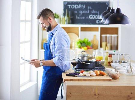 Photo pour Homme suivant la recette sur tablette numérique et la cuisson des aliments savoureux et sains dans la cuisine à la maison. - image libre de droit