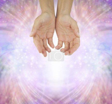 Photo pour Mains d'un guérisseur Humble - femelle remet en position ouverte de creuse sur un fond rose du formation énergie pétillante avec espace copie ci-dessous - image libre de droit