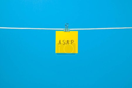 Paper note on clothesline with text over colorful background