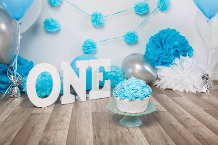 Festive background decoration for birthday celebration with gourmet cake, letters saying one and blue balloons in studio, cake smash first year concept