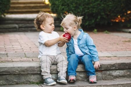 Photo pour Portrait de deux bambins mignon adorables enfants drôle caucasien blancs, assis ensemble partage, eating apple, amour amitié enfance concept, meilleures amies pour toujours - image libre de droit