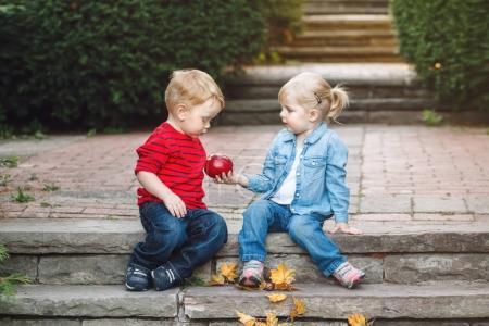Photo pour Portrait de groupe des deux bambins mignon adorables enfants drôle caucasien blancs, assis ensemble partage apple alimentation amour amitié enfance concept meilleures amies pour toujours - image libre de droit