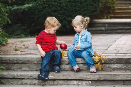 toddlers sitting together sharing  apple