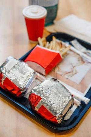 burgers wrapped in tinfoil, french fries