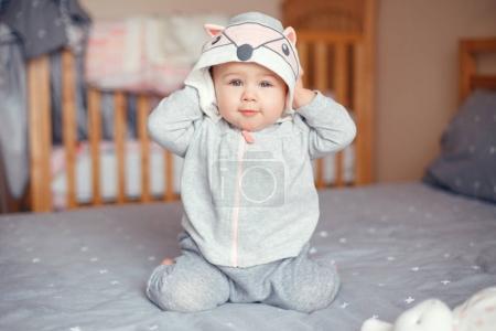 Photo pour Portrait de mignonne adorable blonde caucasienne souriante bébé fille aux yeux bleus en pyjama gris avec capuche d'animal de chat renard assis sur le lit dans la chambre. Concept de mode de vie enfant heureux . - image libre de droit