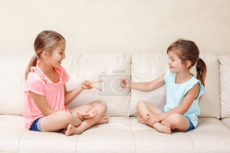 Two girls friends playing rock paper scissors hand game. Caucasian children sitting on couch playing together. Interesting entertaining activity for kids. Authentic candid lifestyle moment.