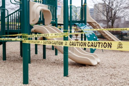 Photo for Toronto, Ontario, Canada - March 26, 2020: Closed outdoor playground. Kids play area locked with yellow caution tape to stop people gathering. Coronavirus social distance quarantine. - Royalty Free Image