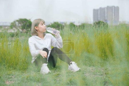 Photo pour Asiatique jeune femme hydratant pendant l'exercice dans l'espace vert urbain - image libre de droit