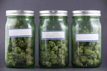 Cannabis glass jars over grey background - medical marijuana dis