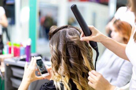 Photo pour Styliste de près fait une fille client coiffage ondulation de cheveux avec des fers à friser dans un coiffeur. client fille regarde dans smartphone dans flou. gros plan, gros plan . - image libre de droit