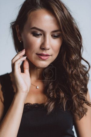 Photo for A close-up portrait of a brown-eyed brunette woman of 32 years with beautiful healthy hair in a black top on a white background. Soft selective focus. - Royalty Free Image