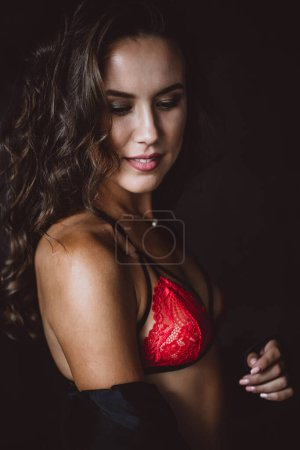 Photo pour Portrait en gros plan d'une femme brune aux yeux bruns de 32 ans avec de beaux cheveux sains en sous-vêtements en dentelle sur fond noir. Choix sélectif souple. - image libre de droit