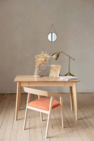 Photo for Table and chair in a modern style in beige colors with a vase of dried flowers and a copper lamp. Home Office. Interior Design. - Royalty Free Image