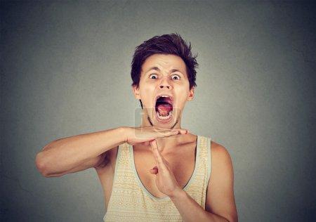 Photo pour Jeune homme montrant expirer geste de la main, criant frustré d'arrêter isolé sur fond de mur gris. Trop de choses à faire accablé. Émotions humaines face à la réaction d'expression - image libre de droit