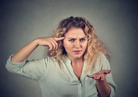 Photo pour Colère fou jeune femme gesticulant avec le doigt contre le temple êtes-vous fou? Isoler sur le fond gris. Émotion négative expression faciale sentiment langage corporel - image libre de droit